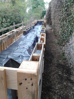 adding the permeable plastic to the raised bed